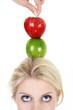 Junge blonde Frau blickt nach oben auf Äpfel