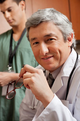 Mature Doctor Holding Glasses