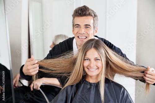 Fototapeta Hairdresser Examining Customer's Hair St Salon