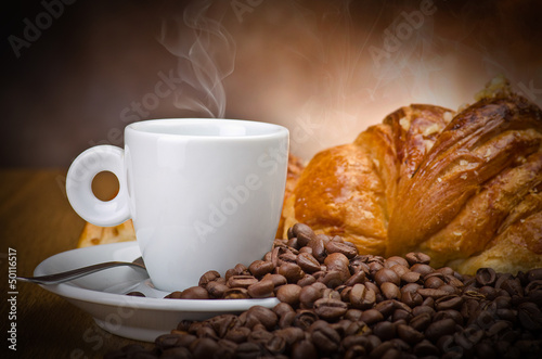 Coffee smoking on the coffee beans and croissant background