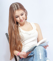 woman sitting on a chair in jeans  reading a book