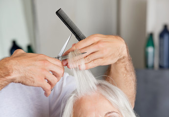 Hairdresser's Hand Cutting Hair In Parlor