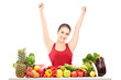 Excited young female gesturing happiness on a table full of frui