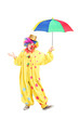 Full length portrait of a cheerful clown holding a colorful umbr