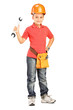 Full length portrait of a child with helmet holding a wrench