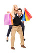 Young man giving a piggyback ride to a woman with shopping bags