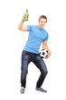 Full length portrait of an euphoric fan holding a beer bottle an
