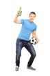 Full length portrait of an euphoric fan holding a beer bottle an