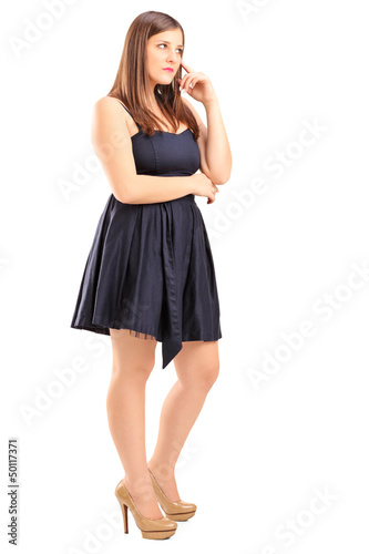 Full length portrait of a young female standing and thinking