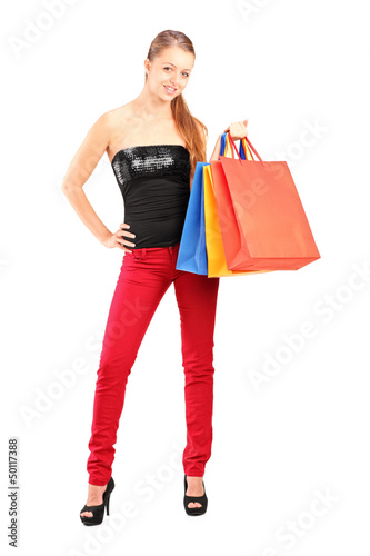 Full length portrait of a young smiling female holding shopping