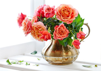 Beautiful fresh roses in a vintage jug .