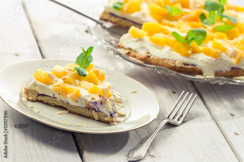 Cake with cream and peaches on a plate