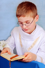 boy going to the first holy communion with prayer book