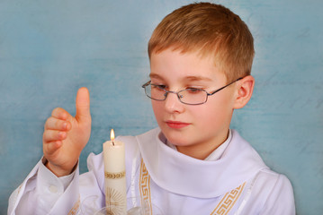 boy going to the first holy communion with a candle