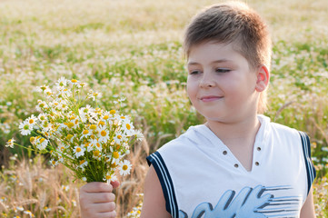 A boy with a bouquet of daisies in a field