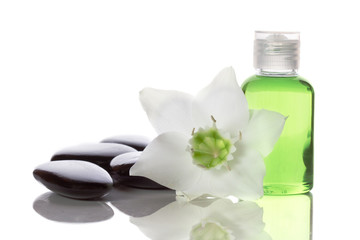 spa items - liquid soap, stones and flower