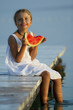 Summer joy, girl eating fresh watermelon on the pier