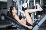 Woman at gym doing exercises to strengthen the muscles of legs poster