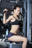 Woman at gym doing exercises to strengthen the muscles of back poster