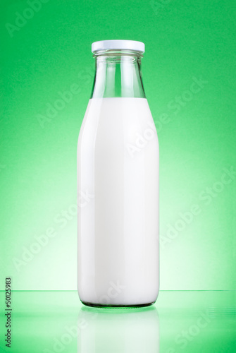 Bottle of fresh milk isolated on a green background
