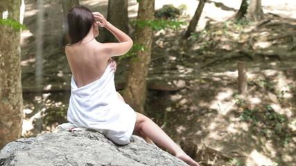 Woman sitting near the waterfall