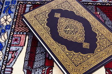 QUR'AN OVER MUSLIM PRAYER CARPET