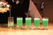 Barman serving green alcohol shots.