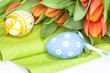 Easter eggs with orange tulips on white background