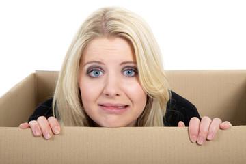 Frau hat Angst und versteckt sich in Karton, wo geht´s hin