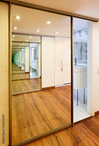 Sliding-door mirror wardrobe in modern hall interior with infini