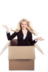 Frau kommt voller Freude überrascht aus Karton, Hilfe ist da