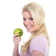 Hübsche junge Frau lacht vergnügt mit Apfel, weiße Zähne