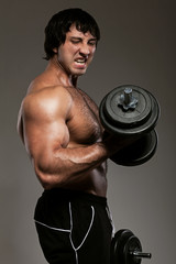 Muscular guy working out with dumbbells