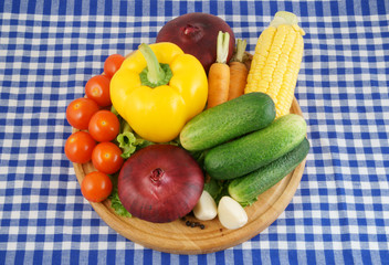 Vegetables on wooden cutting board on tablecloth