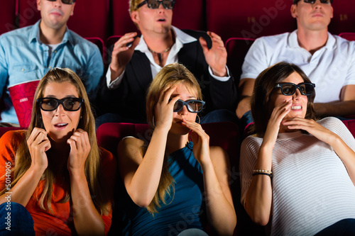 Group of people watching 3d movie at movie theater
