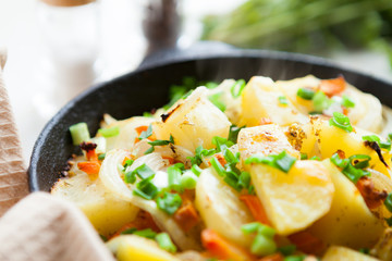 golden pieces of fried potatoes with greens
