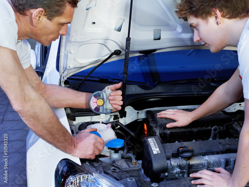 Two car mechanics fixing the engine of a car in a garage