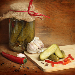 Glass jar with the cucumbers on a wooden table