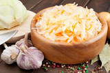 Sauerkraut with carrot in wooden bowl, garlic, spices, cabbage o