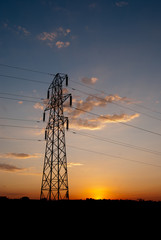 Electricity pylon against orange sunset