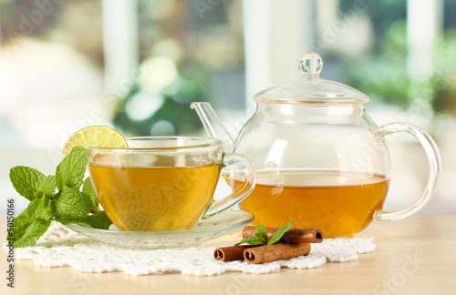 Cup of tea with mint,lime and cinnamon on table in room