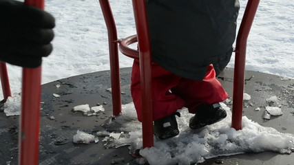 little girl at the playground is turning red circle in winter