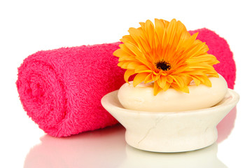 Rolled pink towel, soap bar and beautiful flower isolated