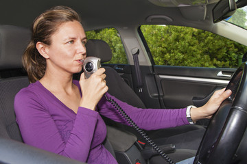 Woman blowing into breathalyzer