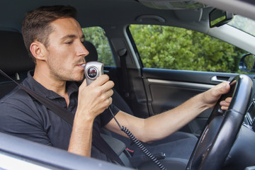 Man blowing into breathalyzer