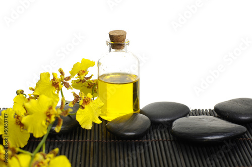 bottles of essential oil with yellow orchid and zen stones