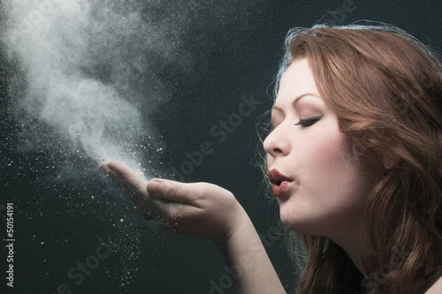 The girl blows off a dust from a palm