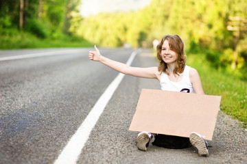 young girl hitchhiking with cardboard
