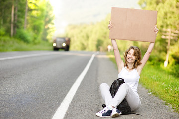 Beautiful young female hitchhiker with cardboard