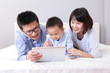 cute boy using tablet pc with happy family